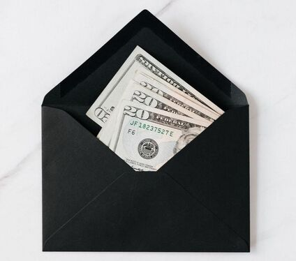 few twenty dollar bills in black envelope