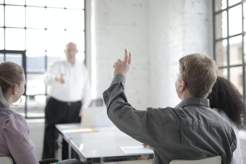 training session with man raising his hand to speak